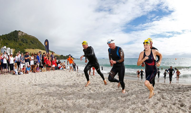Swimmers in wetsuits running across the beach from the water