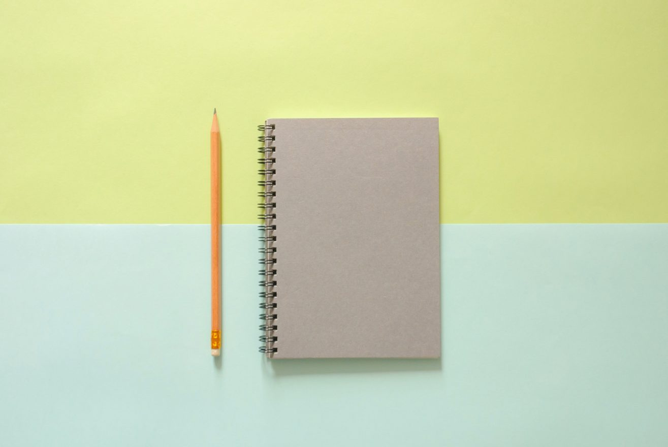 notebook and pencil on a coloured background