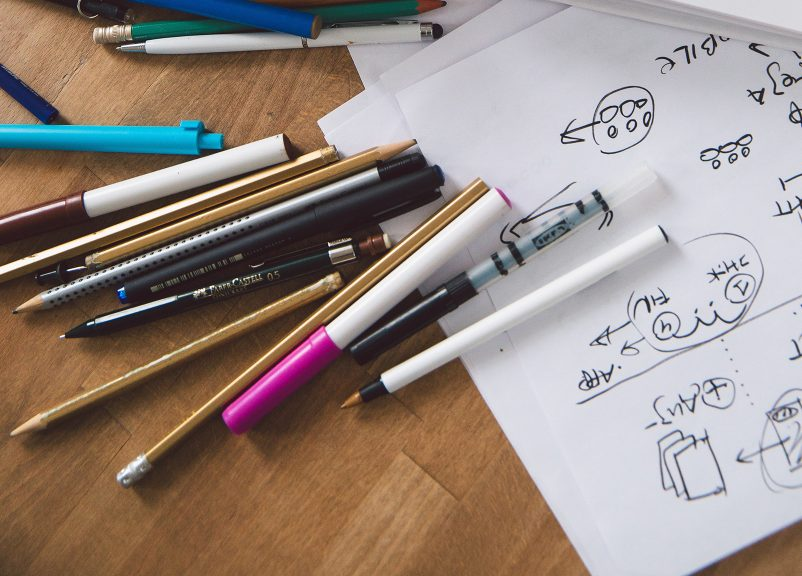 various types of pens scattered on desk with notes made on paper