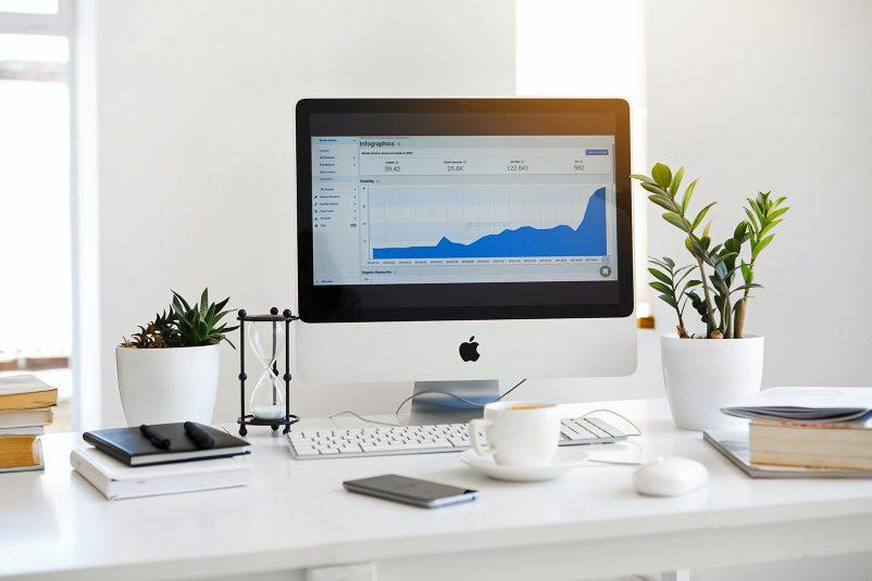 mac computer on desk, showing analytics data on screen