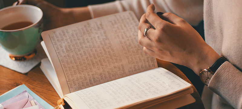 Close up of a book open to pages of hand-written text. A cup of coffee is held in the background